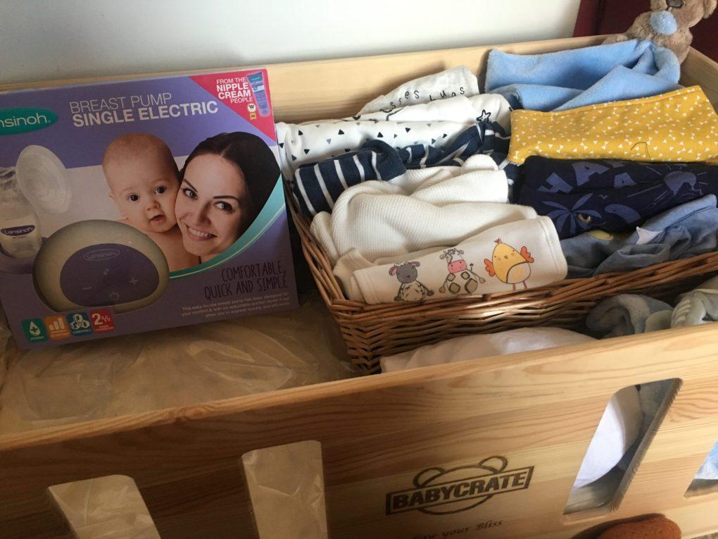 newborn baby essentials in baby crate bed