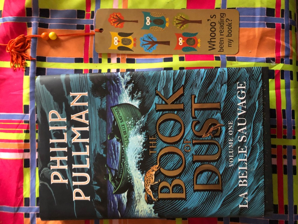 Left; Blue Hardback Cover of La Belle Sauvage, The Book of Dust Book One, Right; Bookmark with Owls