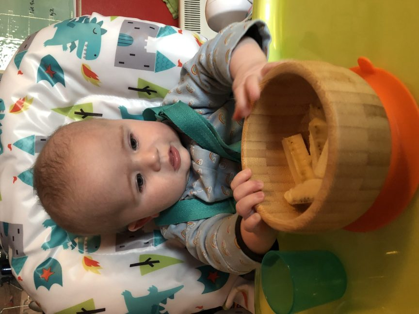 baby boy in Cosatto highchair weaning, eating banana from bamboo bowl