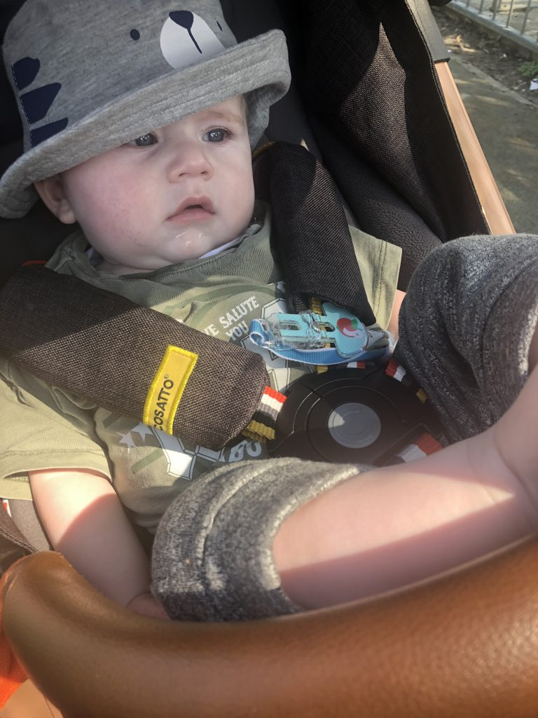 Baby Boy in Cosatto Woosh XL Pram during recent sunshine with cute blue bear hat