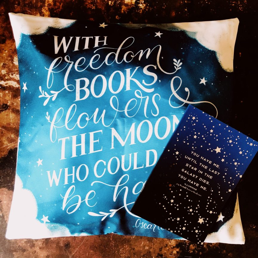 a blue pillow with an oscar wilde quote and blue starry notebook photographed together for an unboxing blog post of the fairyloot book box