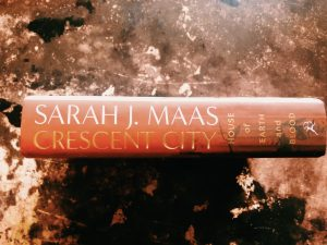 a picture of the spine for sarah j maas' book crescent city house of blood and earth on a copper and brown coloured background