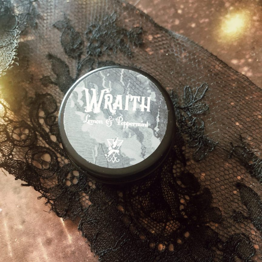 a tinned lipbalm 'wraith' scented with lemon and peppermint against a black lace and copper background