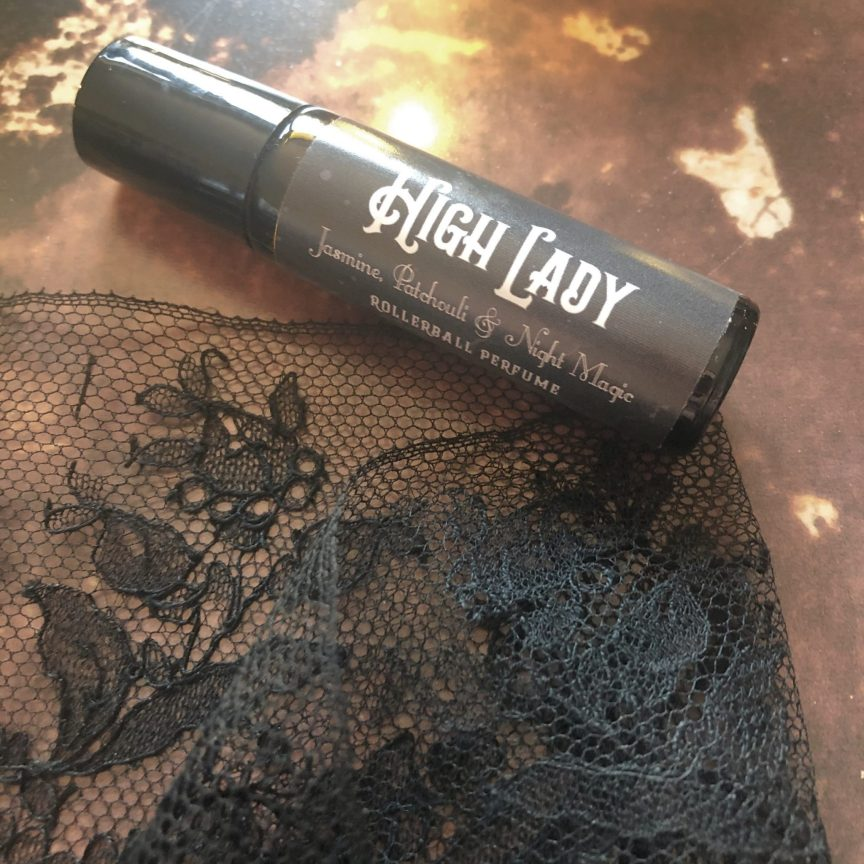 high lady rollerball perfume scented with jasmie, patchouli and night magic pictured against a copper and black lace background