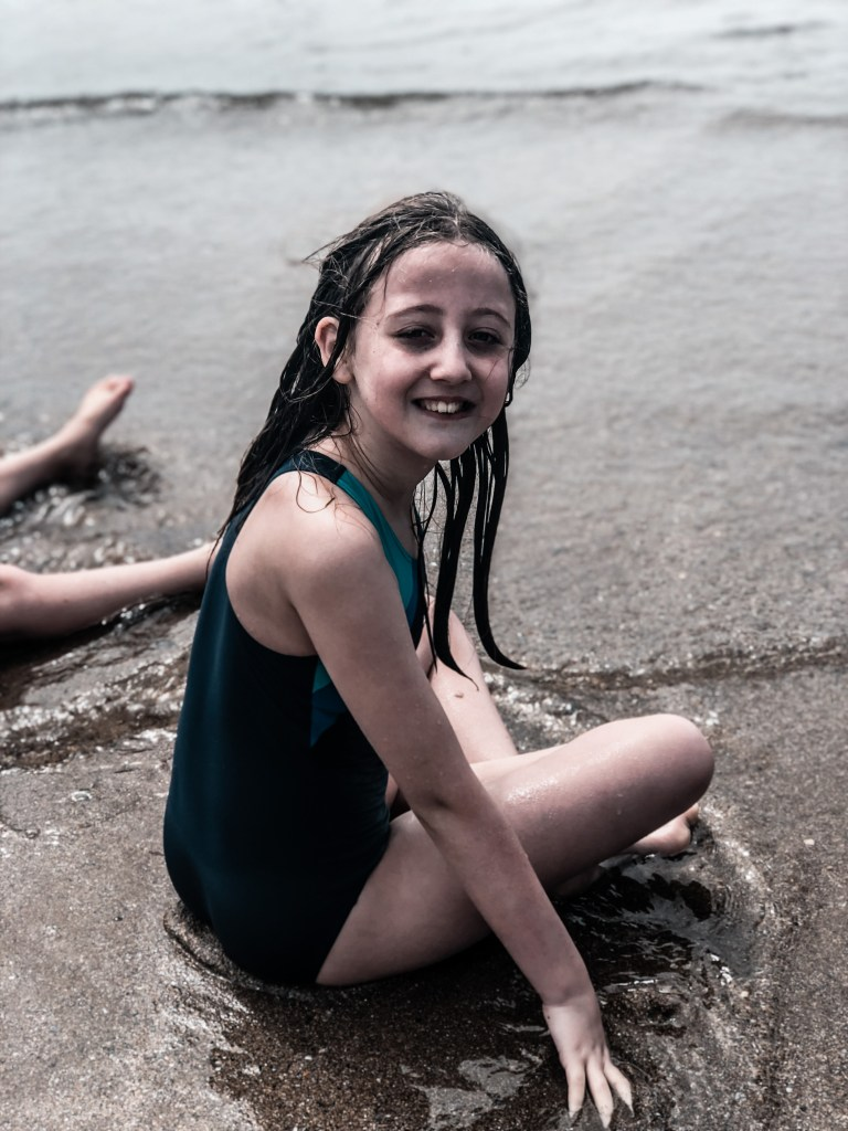 child sitting on the beach in the water after jumping the waves