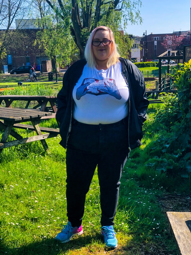 female plus size figure wearing white top, black jeans and blue trainers standing on grass near some water with tall trees in the background
