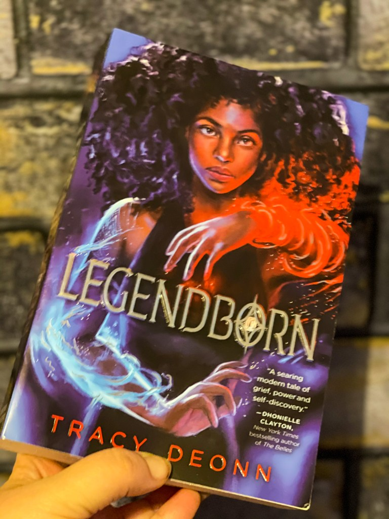 a paperback copy of the book Legendborn by Tracy Deonn against a grey brick background