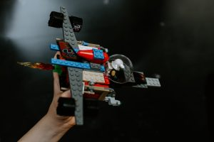 child holding a toy spaceship built from lego