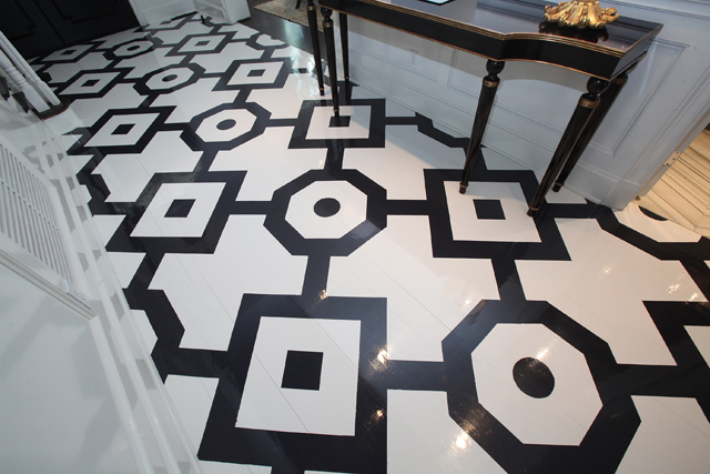 The foyer floor has classic geometric shapes painted on wood.
