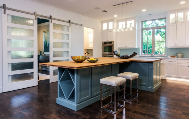 The kitchen in Gilbert's Village Park Eco Home has an airy and light feeling, from the white walls and cabinets to bamboo countertops and contemporary glass pendant lighting. Photo courtesy Michael Hunter Photography.