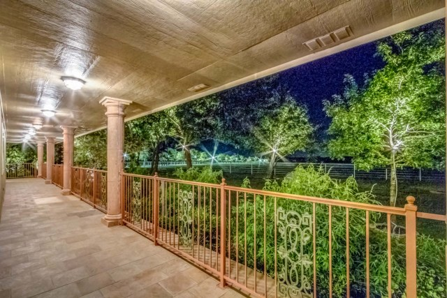 Wrap-around porch looks out over lighted landscape at night.