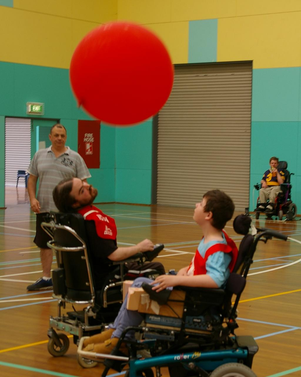 two individuals in electrical wheelchairs playing soccor