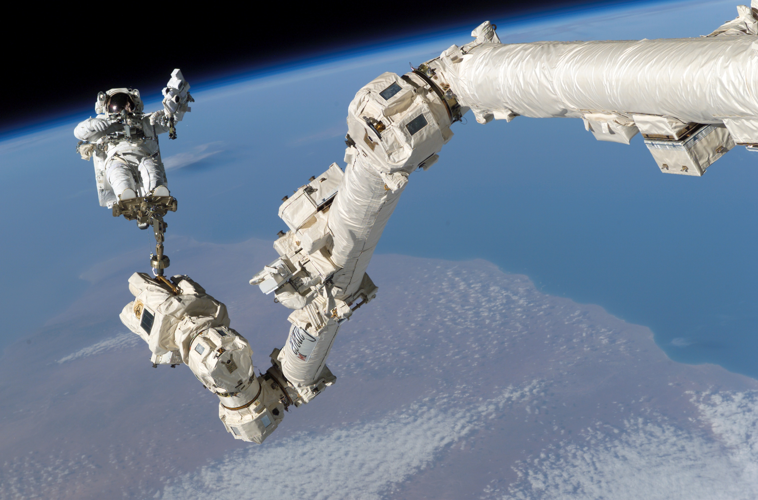 canadarm supporting an waving astronaut in space