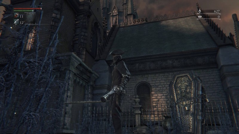 Player character standing with gothic style buildings in background.