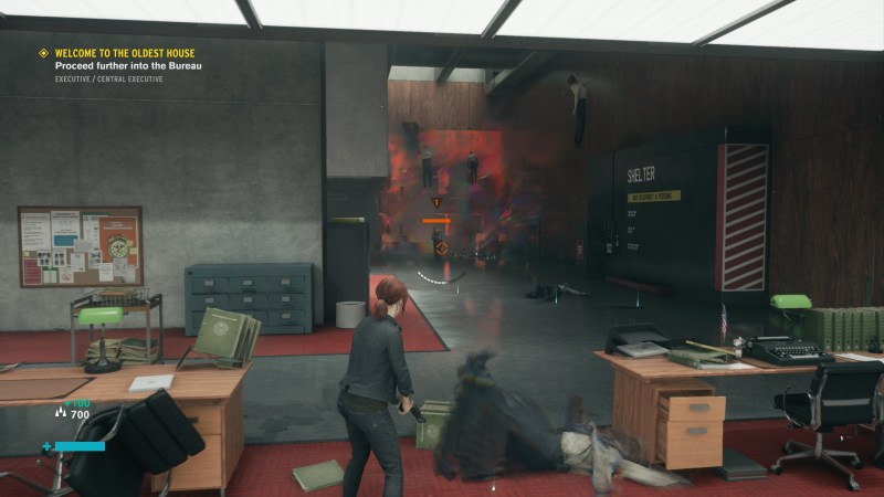 Jesse standing in an office area with an enemy approaching from a red tinted hallway.