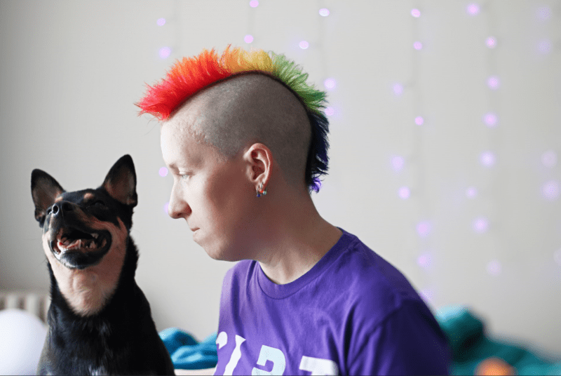 Courtney, wearing a purple CIPT t-shirt, hair in a rainbow colored mohawk, with their dog, Tali, beside them.