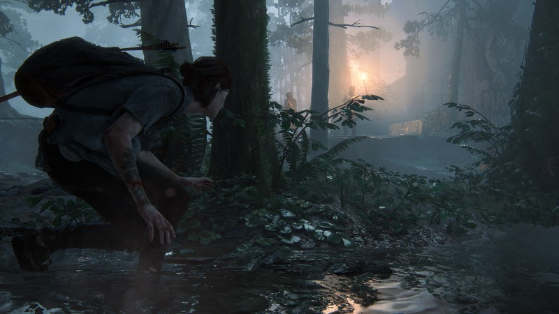 The Last of Us Part 2 - Ellie hiding behind a tree and bushes, looking toward a distant flame in a camp