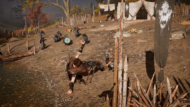 Assassin's Creed Valhalla shot of Eivor being thrown by an enemy, battle erupts in the background between soldiers