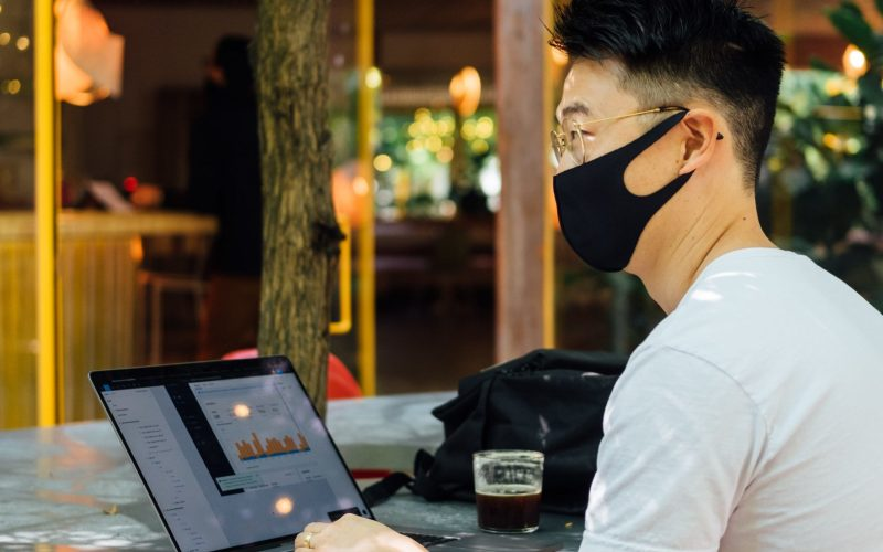 A man sitting at an outdoor table with his phone and laptop on the table, wearing a facemask.