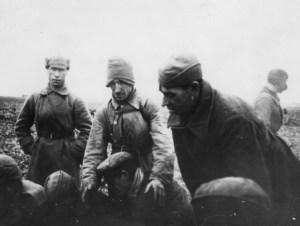 """Część jeńców siedzi na ziemi, czterech ubranych w zimowe szynele, względnie pochyla się. Pierwszy stojący z lewej ma na głowie tzw. """"budionnówkę""""(""""szłom""""), drugi naciągniętą na uszy furażerkę, czwarty czapkę """"uszankę"""" z opuszczonymi nausznikami. [źródło: IPN Rz 19/172]"""