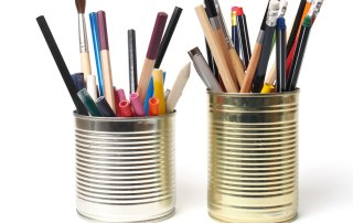 Crayons and pens in waste tin cans on white background