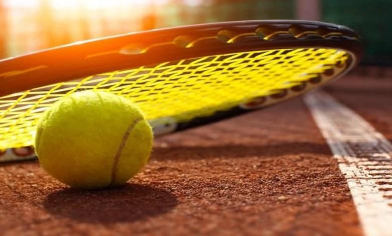 raquette de tennis avec balle par terre