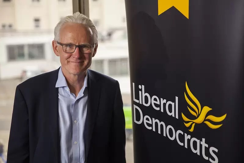 Sir Norman Lamb standing in front of the Liberal Democrats' party poster