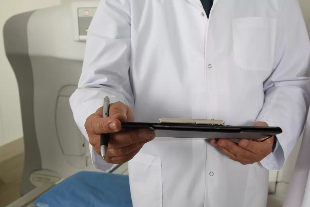 A doctor in a white lab coat holds a clipboard
