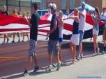 volunteers carry a giant flag in the parade