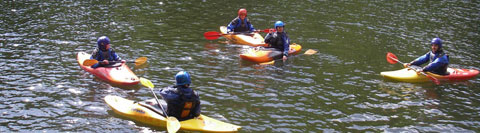 River grading. Five kayakers on flat, moving, grade one water