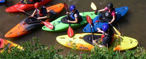 Canoe training in London - many clubs run canoe courses for beginners. Image shows young men and women on a kayak course.