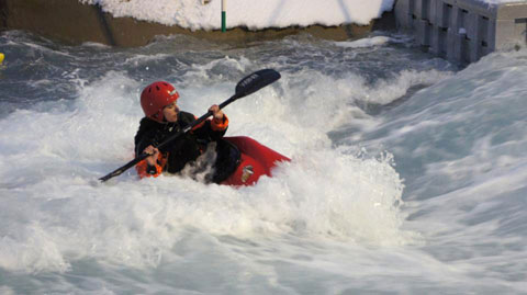 Female kayaker surfs on a wave on the Lee Valley Olympic course