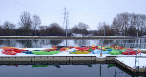 Colouful kayaks lined up on the snow next to the Lee Valley white water course