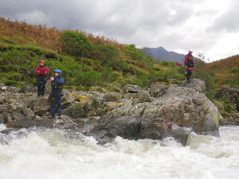 Kayakers inspect a rapid on the river Etive in Scotland