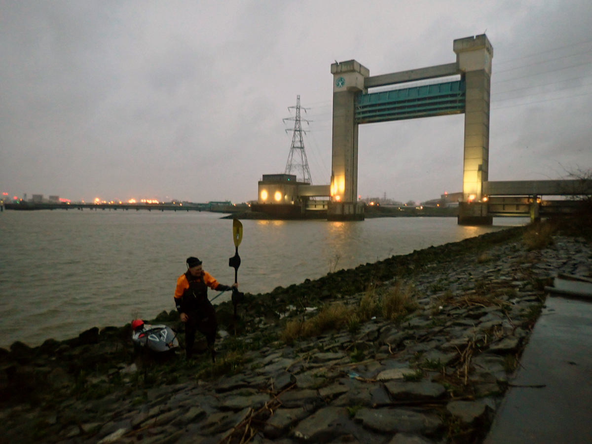 Kayaker pulling their boat up the sloping river edge at dusk, where the Roding meets the Thames.