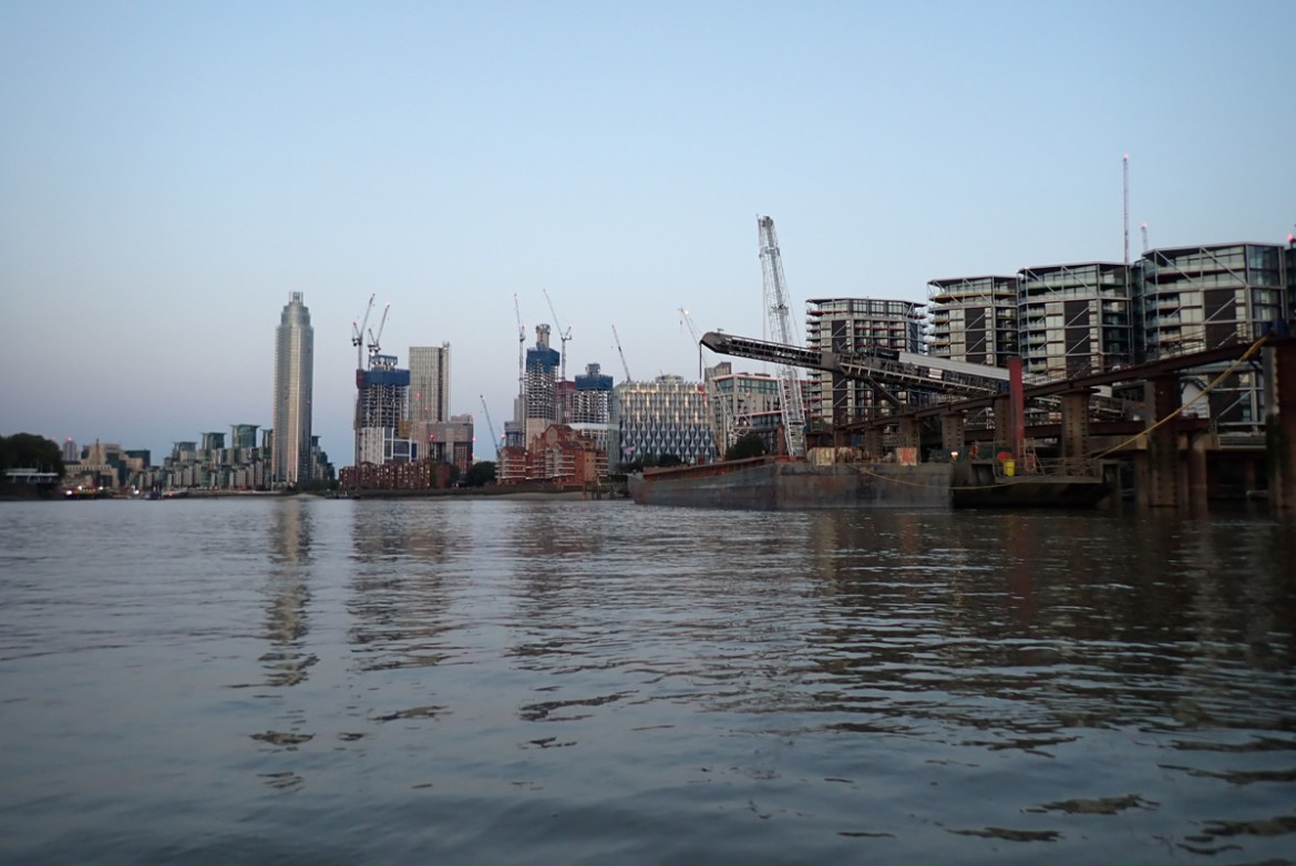 Mid-river view looking downstream towards Vauxhall. The south bank shows newly built apartment blocks and tall cranes
