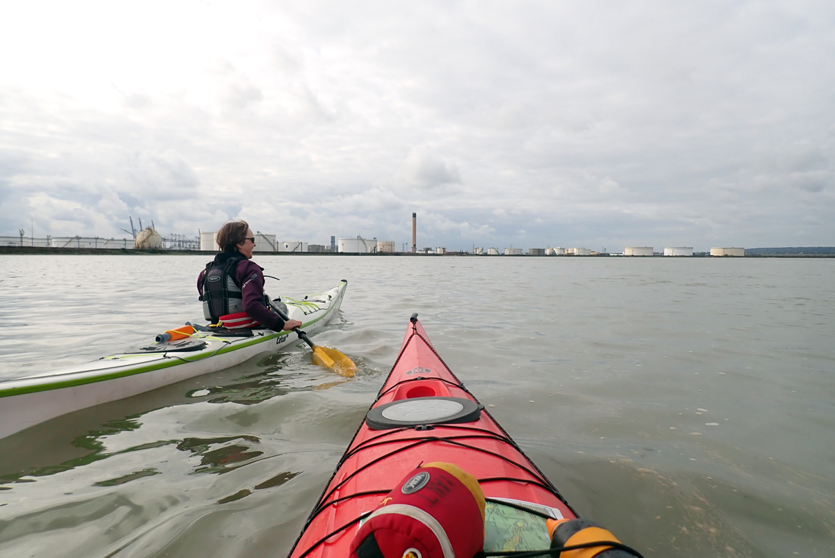 Kayakers paddle past a distant landscape of oil storage tanks, behind a sea wall