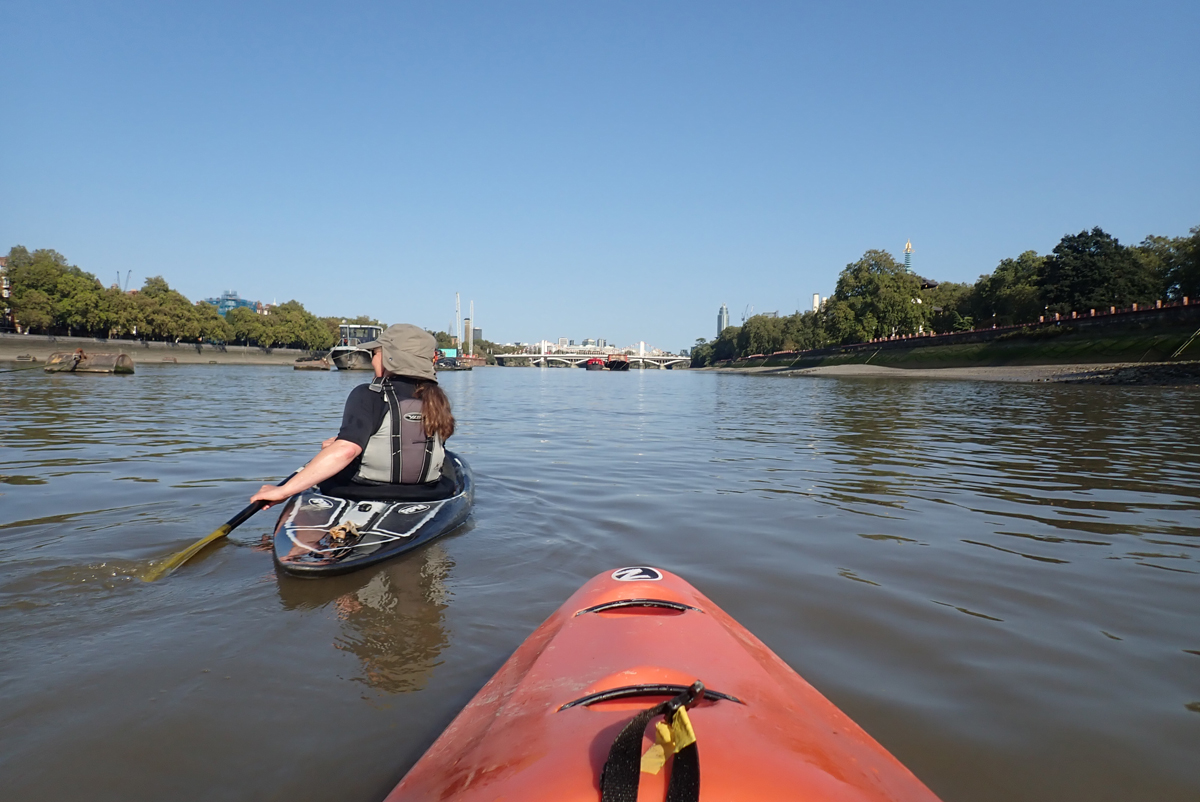 Kayaking on the Thames at Battersea, one kayaker follows the other, on calm water under a blue sky.