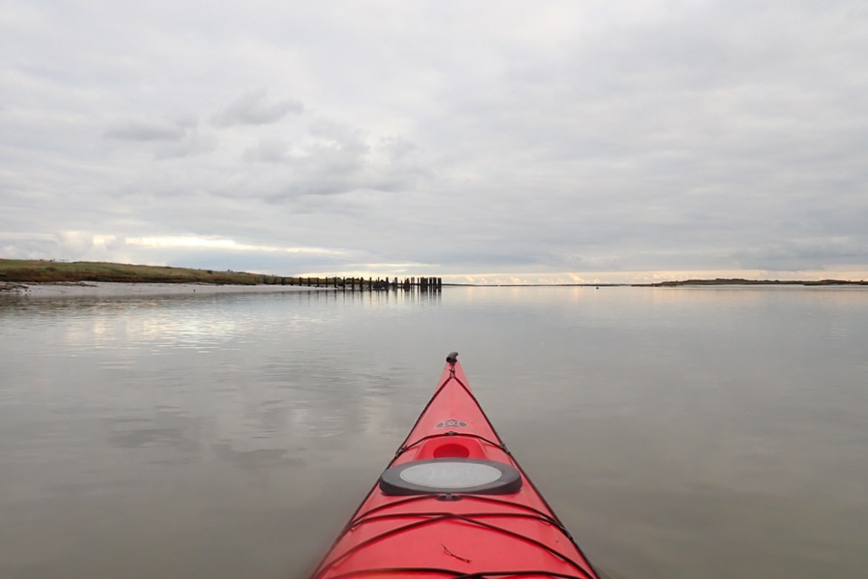 Kayaking along a flat Benfleet Creek past Canvey Island and towards a distant broken wharf