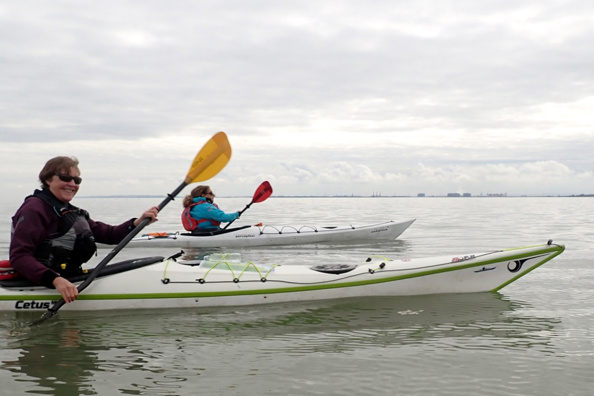 Kayakers on the Thames Estuary, with a ribbon of land in the far distance. The sea is flat and the kayakers are smiling