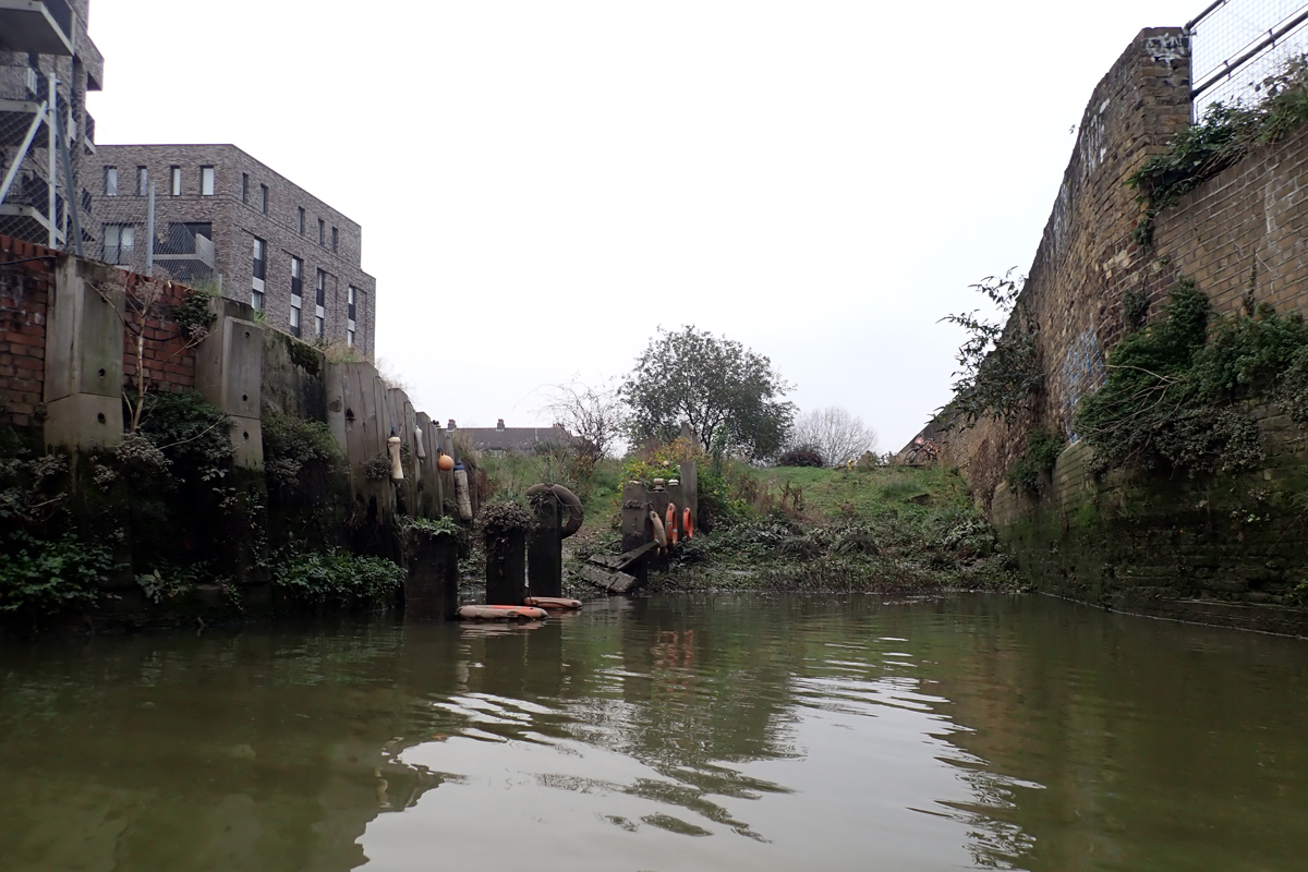 Deptford Creek. An overgrown slipway with a battered brick wall on one side, and modern apartment blocks on the other.