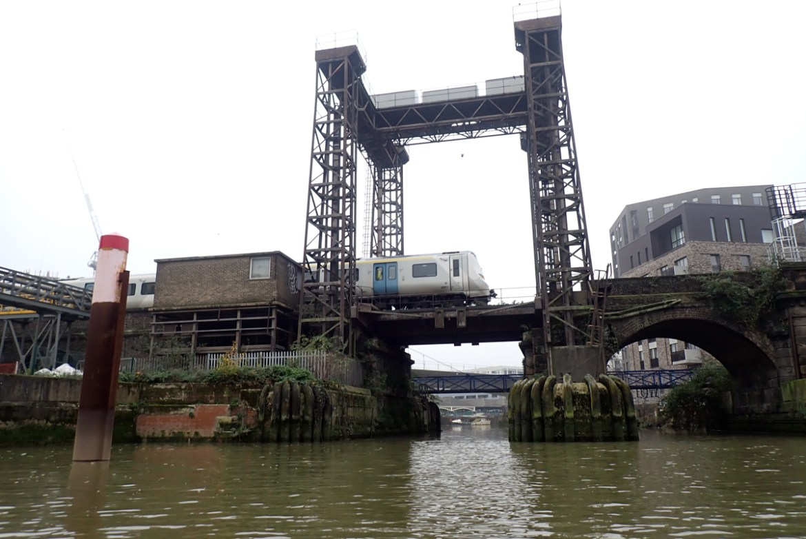 Looking up from the water at the Deptford Creek lifting bridge. The bridge is supported by four tall, latticed towers, which can lift the bridge vertically to allow vessels to pass below.