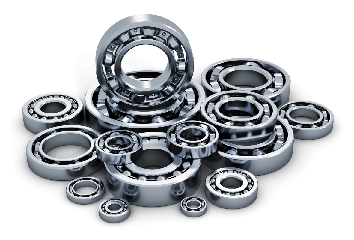 Creative abstract industry, manufacturing and engineering concept: collection of different steel shiny ball bearings isolated on white background