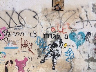 "The graffitti in Tel Aviv covers most alley walls. The yellow popsicle has the tag ""ARTIK"" the Hebrew word for the cold treat."