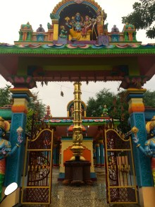 A beautiful and neon colored temple on the side of a dirt road