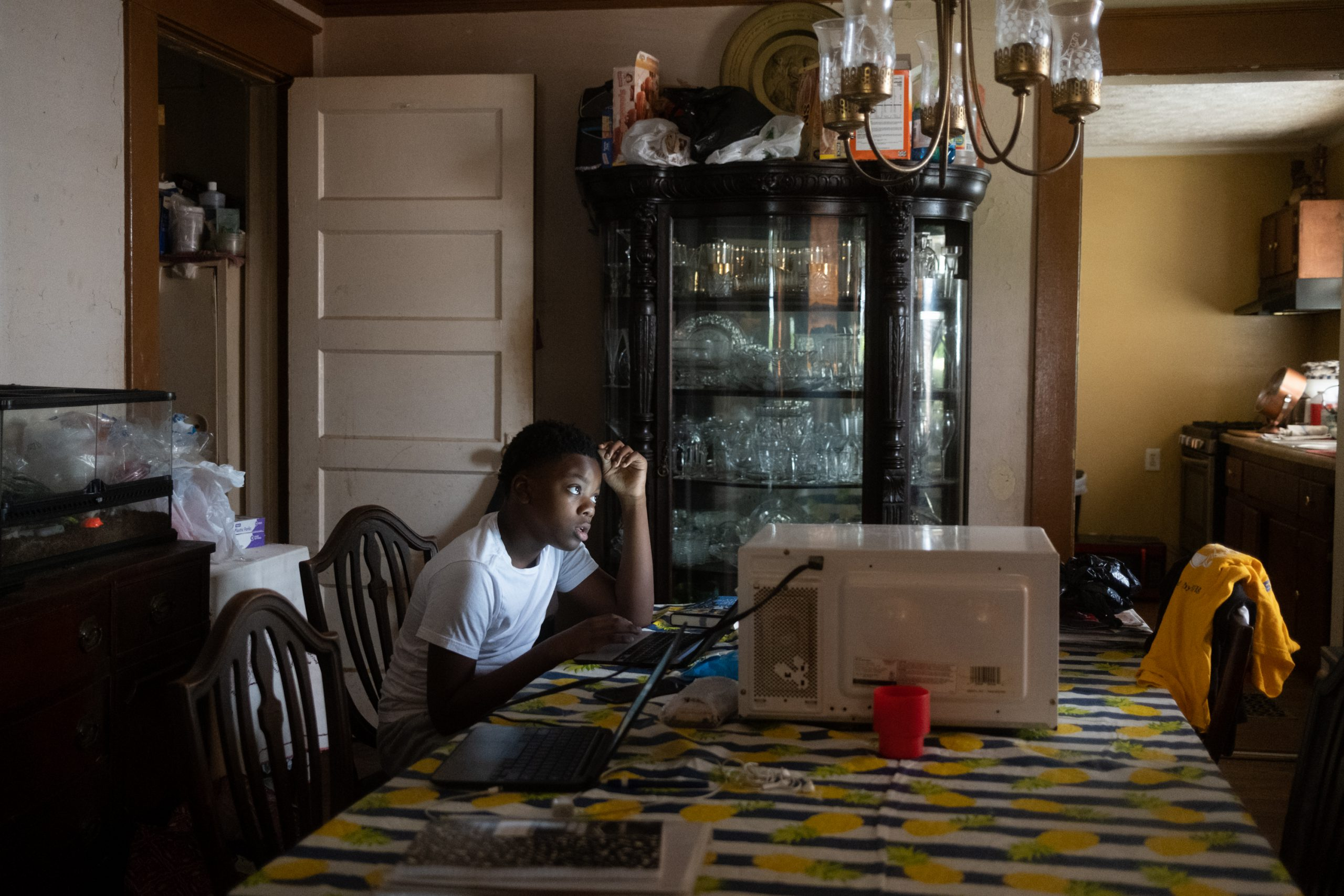 A teenager looks up from his laptop in his dining room