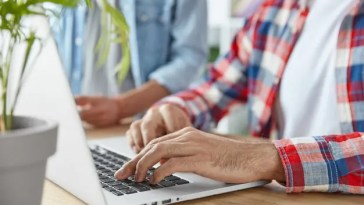 cropped-shot-two-male-bloggers-type-publication-laptop-computer-use-laptop-computer-sit-wooden-desk-young-prosperous-bussinessmen-check-mail-send-feedbacks-connected-wifi_273609-15119