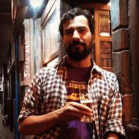 Foto do escritor e tradutor Cesar Alcázar encostado na porta de um bar, à noite, tomando uma cerveja.