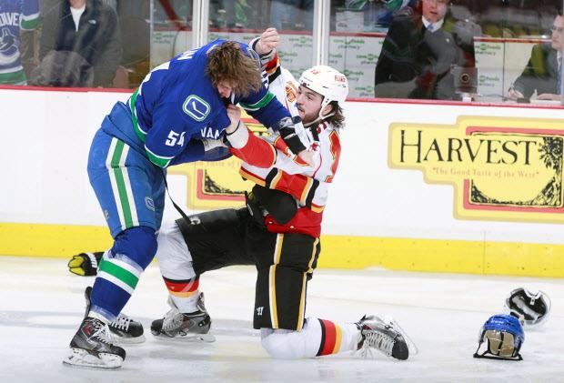 Kellan Lain takes on Kevin Westgarth of the Calgary Flames