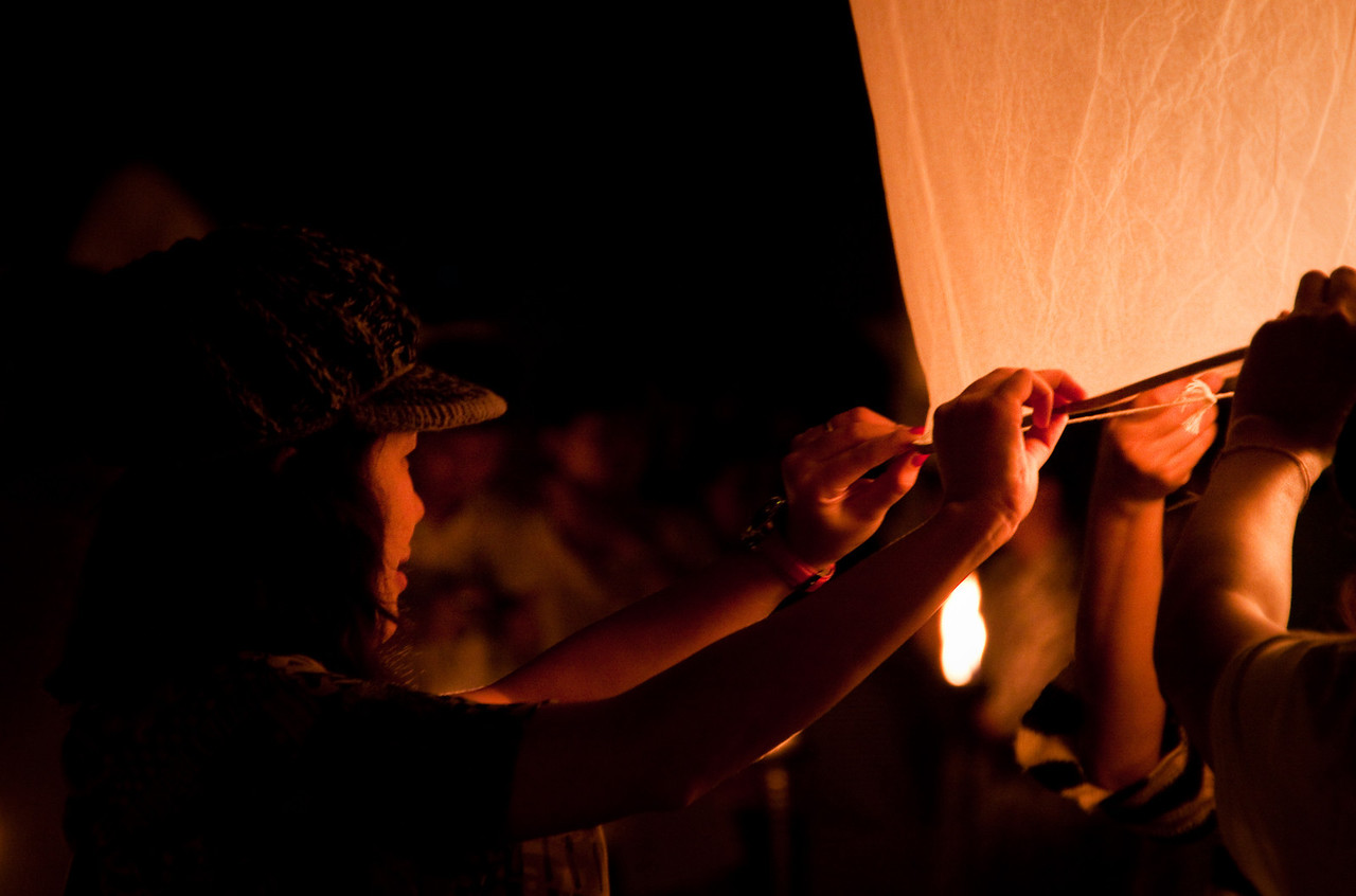 A woman holding a flying lantern with her friends for Loy Krathong festival in Mae Jo, Thailand